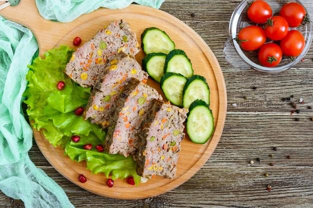 간 캐서롤. 간에서 유용한 요리. 나무 테이블에 쌀과 야채와 함께 갓 구운 돼지 간 수플레.
