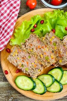 Запеканка из печени. полезное блюдо из печени. свежеиспеченное суфле из свиной печени с рисом и овощами на деревянном столе.