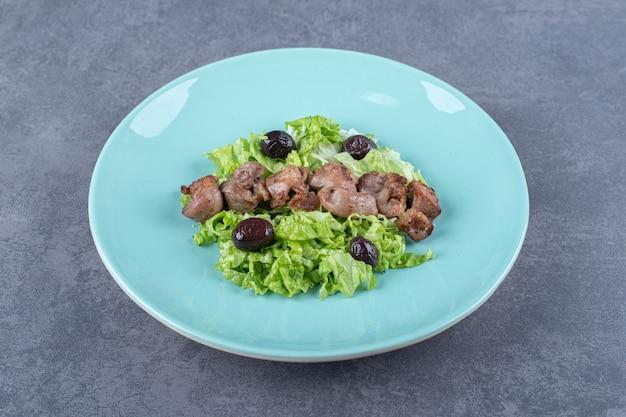 Шашлык из печени и оливки на синей тарелке.