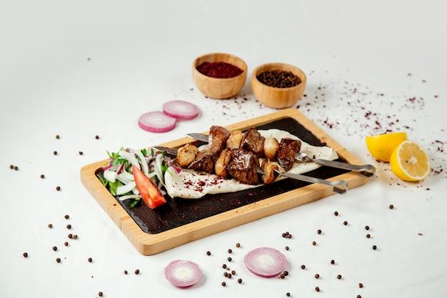 Kebab di fegato con grasso e cipolle su una tavola di legno
