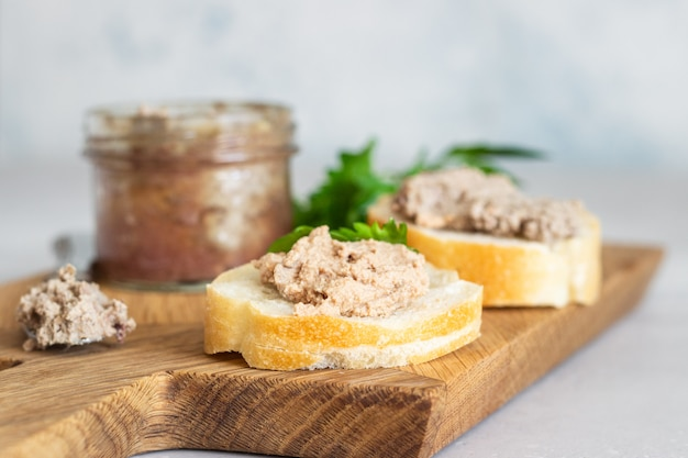 Liver pate in a glass jar with fresh bread and parsley on a wooden cutting board.