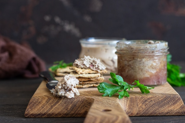 Liver pate in a glass jar with multigrain crackers and parsley.