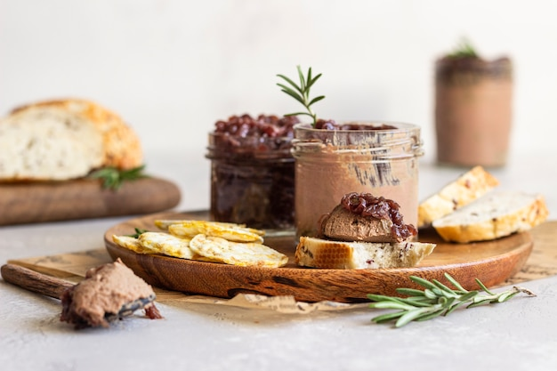 Liver pate and onion chutney in a jar, bread and crackers on a wooden plate