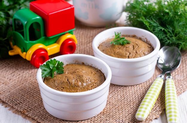 Суфле из печени в белой миске на столе. детские рецепты.