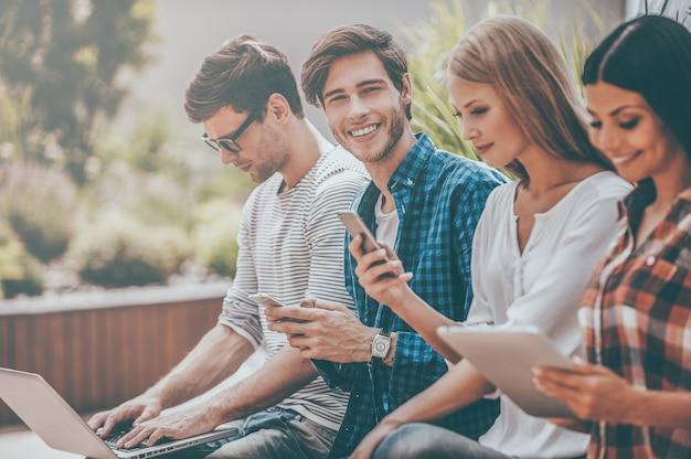디지털 라이프를 살고 있습니다. 남자가 카메라를 보고 휴대전화를 들고 있는 동안 다른 디지털 장치를 들고 있는 젊은 사람들의 그룹