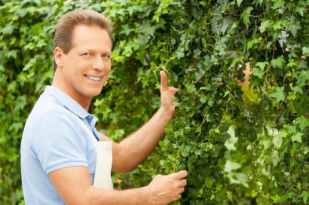 녹색 생활을 살고 있습니다. 제복을 입은 잘생긴 성숙한 남자가 정원을 가꾸고 카메라를 보고 있다