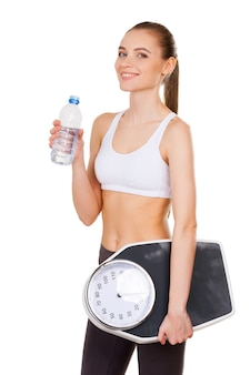 健康的な生活を送る。白で隔離された状態で立っている間、体重計と水でボトルを保持しているスポーツ服の魅力的な若い女性