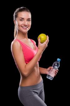 健康的な生活を送る。黒い背景に立っている間、水でリンゴとボトルを保持している幸せな若い女性