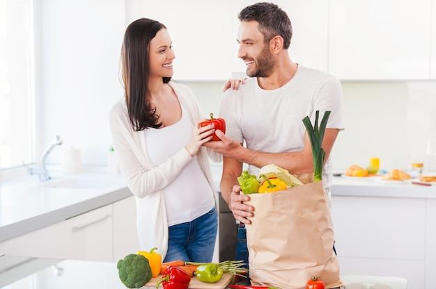 一緒に健康的な生活を送る。新鮮な野菜でいっぱいの買い物袋を開梱し、一緒にキッチンに立って笑っている美しい若いカップル
