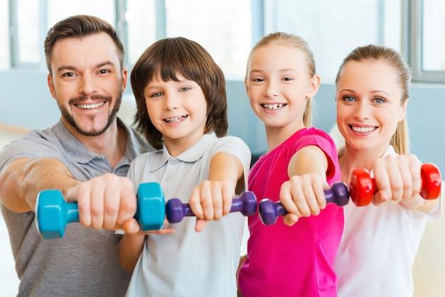 一緒に健康的な生活を送る。ヘルスクラブで互いに近くに立っている間、さまざまなスポーツ用品を持っている幸せな家族