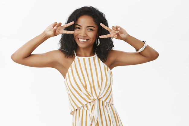 Living joyful life. portrait of bright happy and stylish african american woman in striped yellow overalls smiling broadly showing peace