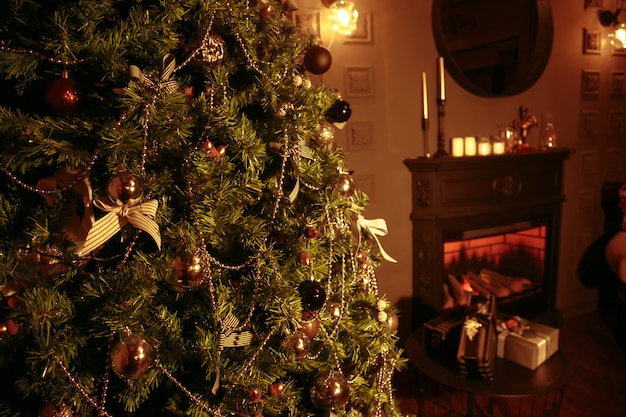 A living room at christmastime lit only by the fire and christmas tree