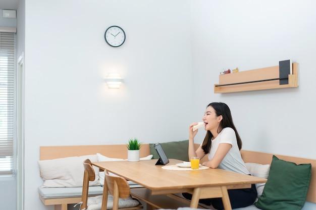 거실 개념은 직장 휴식 시간에 온라인 미디어를 시청하는 샌드위치와 오렌지 주스를 즐기는 여성 성인입니다.