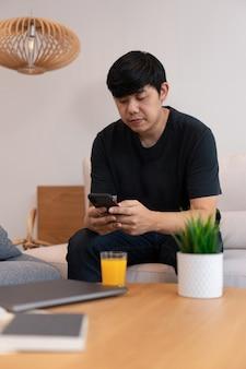 リビングルームのコンセプトリビングルームでスマートフォンと一緒に時間を過ごすクリーム色のソファに座って黒を着ている男性の若い大人。