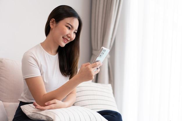 거실 컨셉은 편안한 소파에 앉아 있는 예쁜 소녀가 거실에서 주스와 간식을 먹으며 온라인에서 여가를 보내고 있습니다.