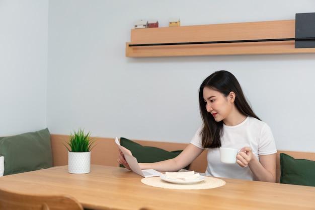 リビングルームのコンセプトは、リビングルームでカフェイン飲料のカップを持っている別の手で読むために紙を持っているきれいな女性。