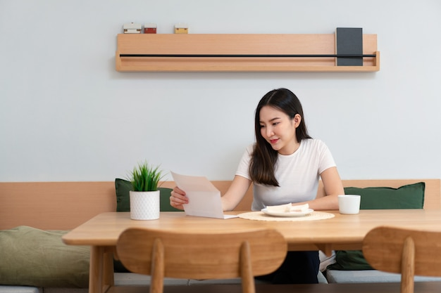 Концепция гостиной симпатичная дама, держащая бумагу для чтения, в то время как другая рука держит чашку напитка с кофеином в гостиной.