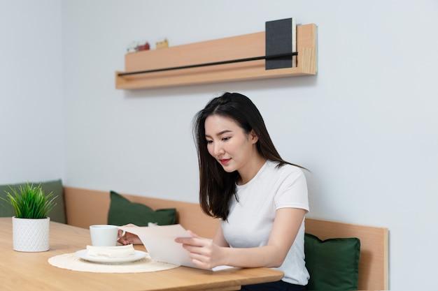 거실은 아침에 다른 손으로 카페인 음료를 들고 있는 동안 신문에 있는 기사를 읽는 예쁜 여성입니다.