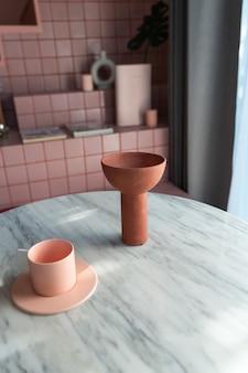 클레이 세라믹 꽃병과 핑크 타일 계단이있는 흰색 대리석 테이블에 베이비 핑크 컵으로 장식 된 거실 코너