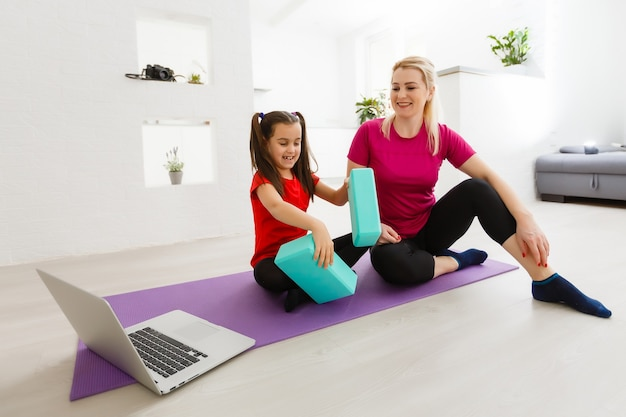 自宅でエクササイズをしているリビングルームフィットネストレーニングの女の子。筋肉を鍛える若い女性、ジムに行かなくても健康的なライフスタイル。