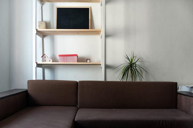 밝은 색상의 거실. 갈색 소파와 나무 선반. 내부
