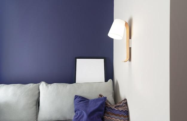 Интерьер гостиной в стиле минимализма с нежно-синими стенами, диваном с тканевыми подушками, светильником на стене и рамой для макета.