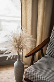 リビングルームのインテリアデザイン。審美的な家、アパートのコンセプト。ミッドセンチュリースタイルの椅子、カーテン付きの窓の近くの土鍋のパンパスグラス