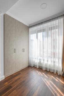 스튜디오 아파트의 일부로 현대적인 스타일로 디자인 된 거실 인테리어, 창문 및 옷장 전망