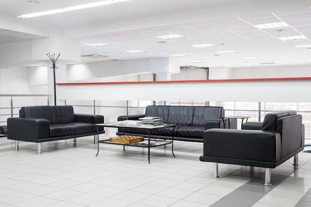 壁、天井、床の白いデザインの手作りの黒革のソファのあるレセプションのリビングルームのインテリア。オフィスのゲストのためのレセプション