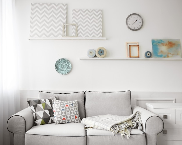 Living room interior, grey couch and shelves with paintings on wall