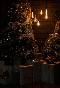크리스마스 트리와 저녁 시간에 선물 상자가있는 밝은 빈티지 램프가있는 거실 인테리어. 새해를 기다리고 있습니다.