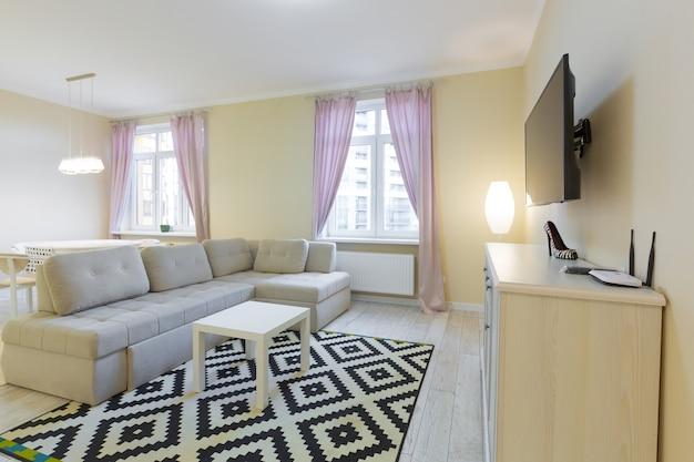 Интерьер гостиной, с большим диваном и телевизором, с фиолетовыми шторами, современный стиль в светлых тонах.