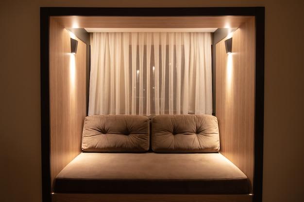 ソファと照明付きのリビングルームのインテリア、枕と柔らかな照明付きの茶色のソファ。夕方、夕暮れ。