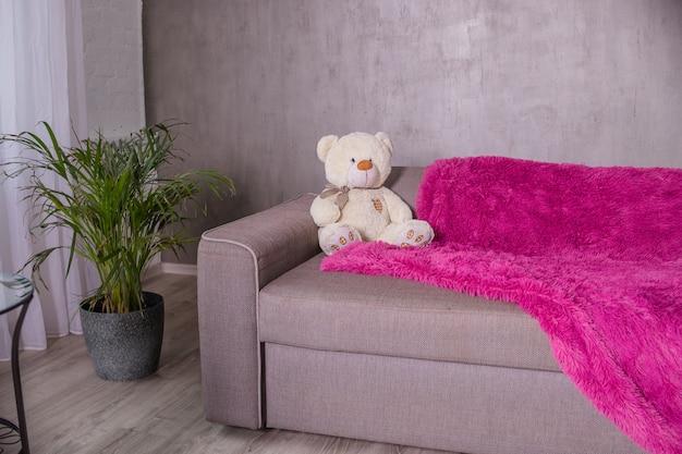 Living room. teddy bear sitting on sofa , purple blanket, plaid.
