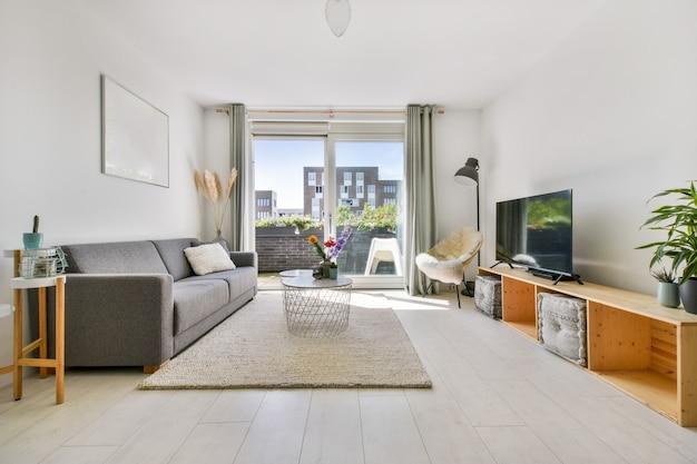 カーペット、マイルドなソファ、テーブル、その他の豪華な家具とテレビを備えたリビングルーム
