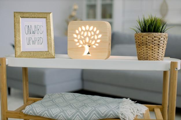 회색 소파와 사진 프레임이있는 트렌디 한 커피 테이블, 나무 그림이있는 장식용 나무 램프 및 고리 버들 화분에 녹색 식물이있는 거실.