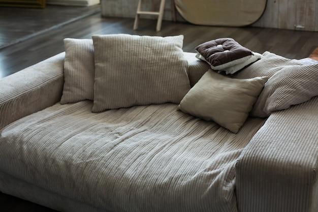 古いベージュのベロアソファと枕のあるリビングルーム