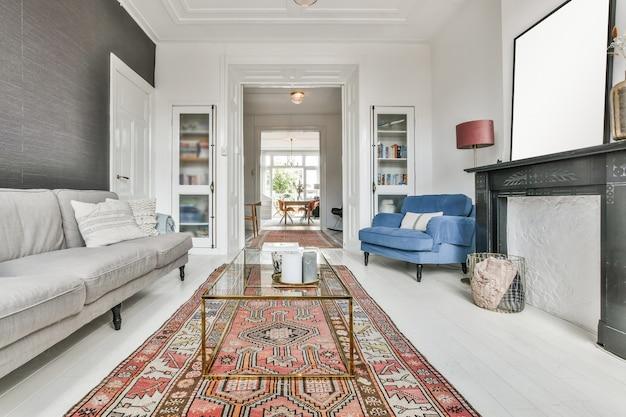 Гостиная с красной ковровой дорожкой, мягким диваном, стеклянным столом и другой мебелью.