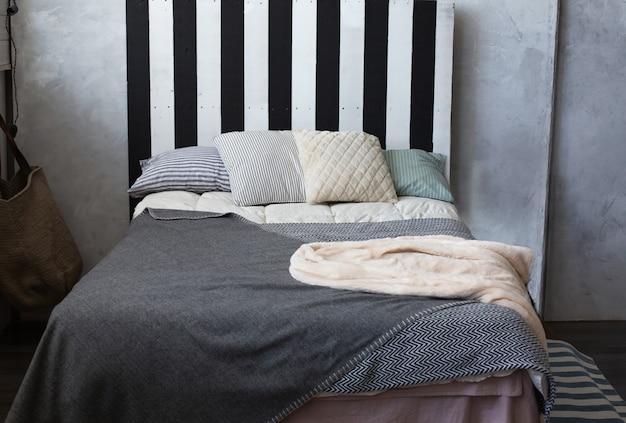 キングサイズベッドにストライプの枕を備えたリビングルーム