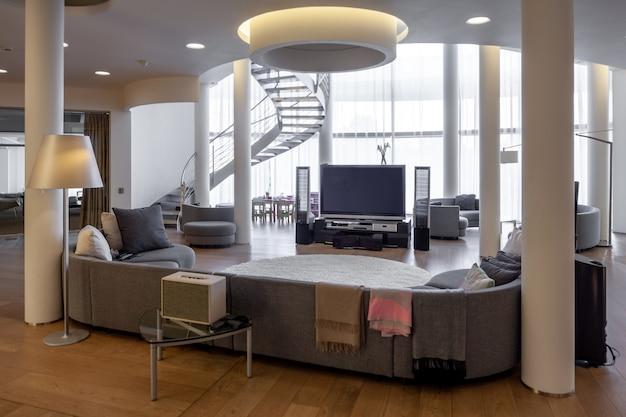 Гостиная с телевизором и домашним кинотеатром, мягким уголком и винтовой лестницей.