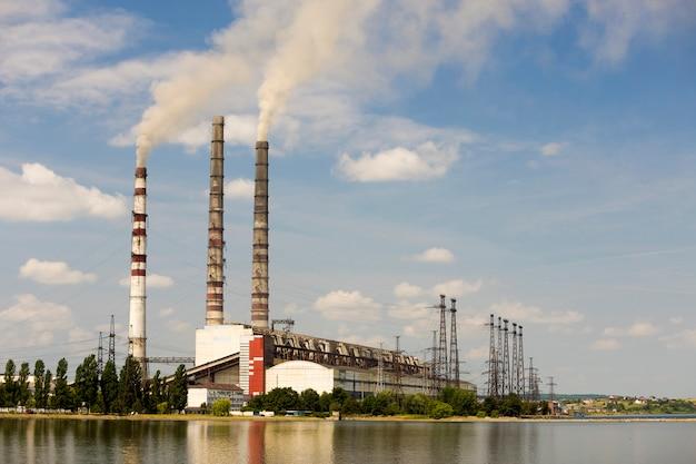 濃い煙のある火力発電所の背の高いパイプは、lkeの水面に反映されます。環境コンセプトの汚染。
