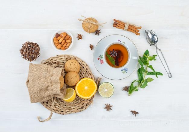 차 한잔, 아몬드 한 그릇 및 차 여과기가있는 둥근 플레이스 매트에 라임과 쿠키
