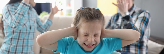Llittle girl in fear closes her ears so as not to hear her parents swear