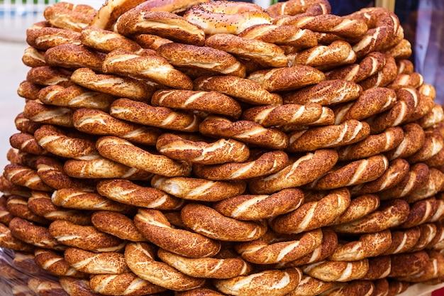 Куча хрустящих симитов кунжута у уличного торговца в стамбуле, турция. турецкий бублик как фон