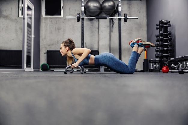 Нагрузка на отжимания и положение планки. вид сбоку привлекательной стройной женщины в спортивной одежде и в хорошей форме, делающей упражнения для рук в крытом тренажерном зале. стабильность тела, гибкость мышц и спортивная жизнь