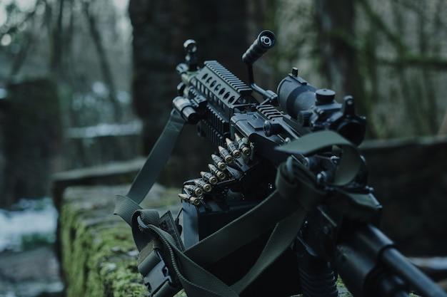 Заряженное страйкбольное оружие крупным планом в лесу Premium Фотографии