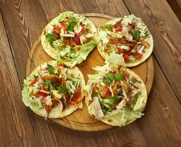 Тостадас с курицей, начиненный сыром, помидорами, гуакамоле, оливками и перцем халапеньо, - отличный способ попробовать начо.