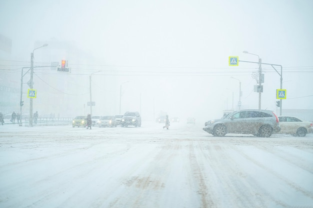 A loaded with traffic highway during massive snowfall, cars, pedestrian, road