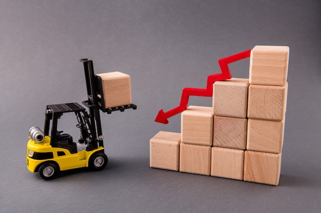 Loader carry wooden cube commerce reduce profit arrow point down