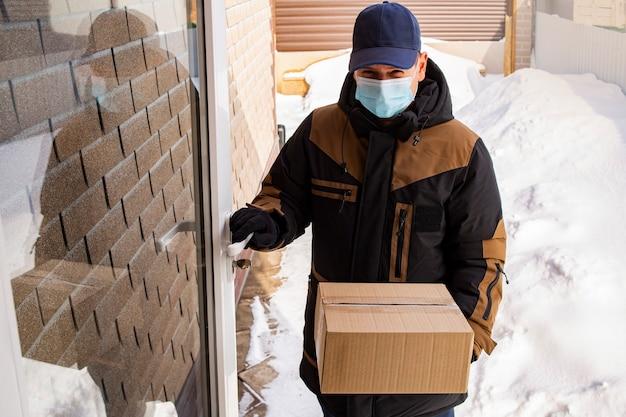 仮面をかぶったローダー配達人の若い男がドアを開け、段ボール箱を家に持ち込みます